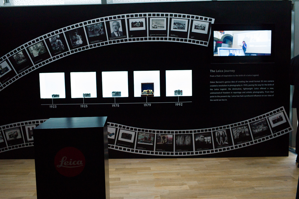 A large wall features the history of Leica cameras, and has video screens playing Leica videos and product announcements.