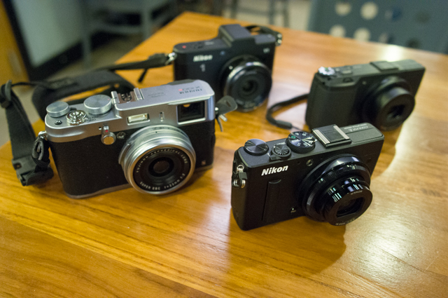 The Fujifilm X100S, Nikon Coolpix A and Ricoh GR being reviewed. The Nikon 1 V1 photobombed the group shot by showing up at the back.